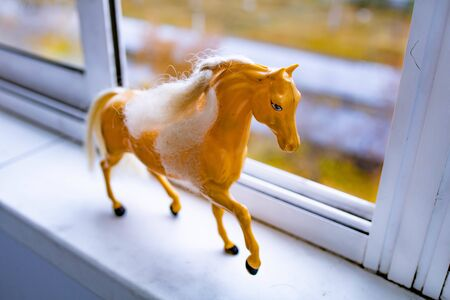 Beautiful little red horse figurine standing at the window