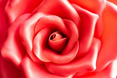 Background texture of a red artificial rose. Artificial red rose bud close-up