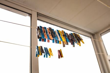 colorful clothespins hang on a rope near the window