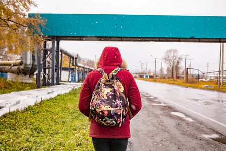 A man with a backpack in a red jacket is walking along the road in autumn weather
