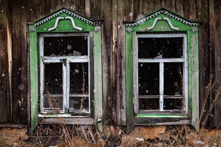 broken windows of an old wooden house. Windows of a country house with broken glass