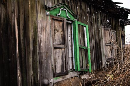 broken windows of an old wooden house in snowfall. Windows of a country house with broken glass