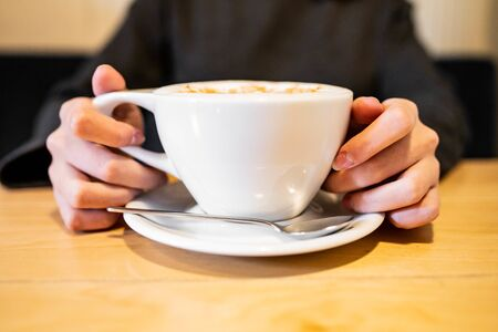 female hands holding a cup of coffee on a wooden table.