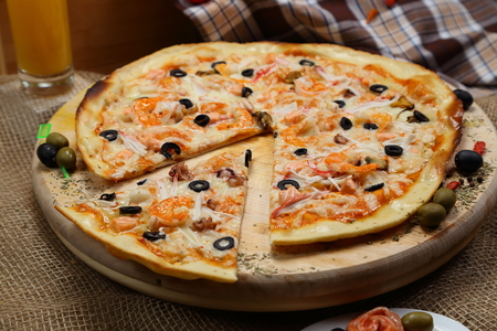 pizza thin olive shrimp crabs on a wooden stand Imagens