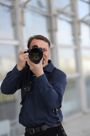 Work of the photographer. A man looks at the camera lens. Journalist.