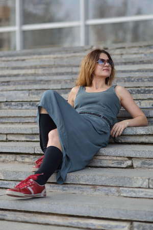 A woman is lying on the stairs with glasses.