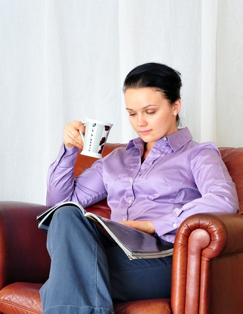 beautiful young girl drinking coffee and reading magazine