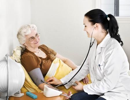 Senior dame ayant tension artérielle par un médecin