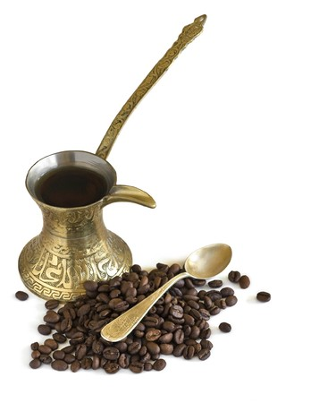 Arab small copper coffee pot with coffee beans. Isolated on white
