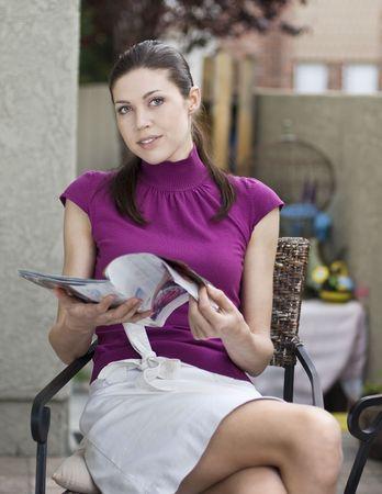Belle jeune femme lisant un magazine