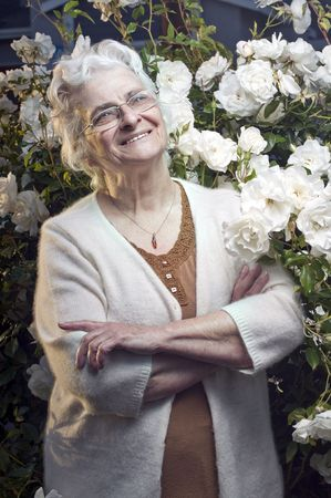 Happy senior lady in the rose garden looking up Stock Photo