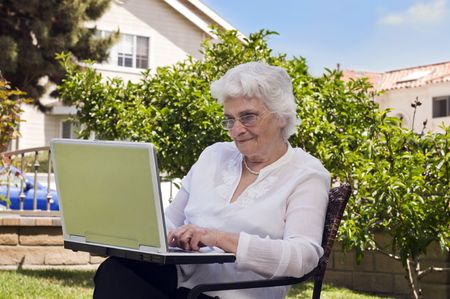 Senior woman sitting in the garden at home and using a laptop Фото со стока