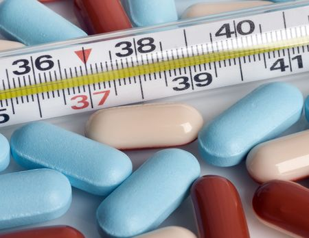 Close up on the medical thermometer with pills