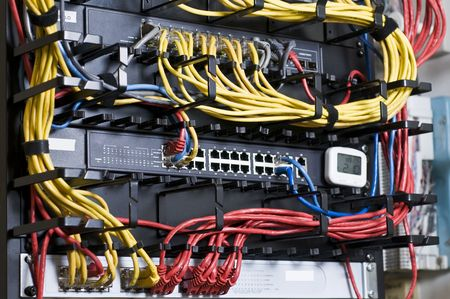 racks: Network hub and patch cables in the rack Stock Photo
