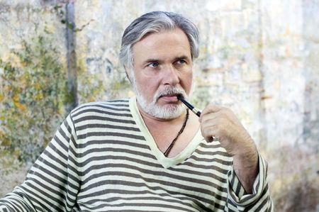 Portrait of a mature man smoking tobacco pipe