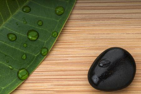 Feuilles vert et Pierre noir avec des gouttes de pluie sur le fond de bambou