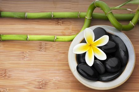 Spa still life background, with flower, bamboo and massage stones