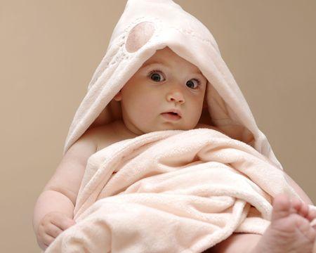 Beau bébé enveloppé dans une couverture rose après bain