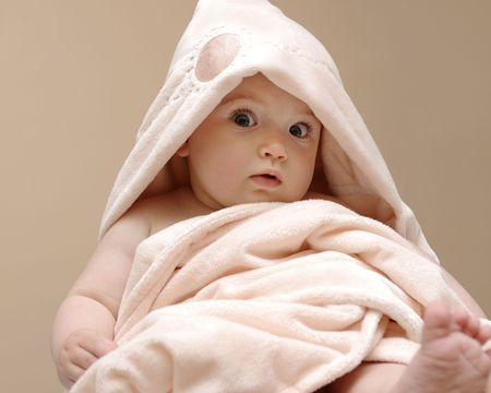 Beautiful baby wrapped in a pink blanket after bath photo