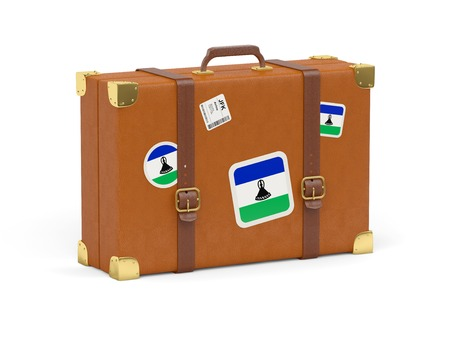 Travel suitcase with flag of lesotho isolated on white photo