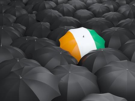 cote d ivoire: Umbrella with flag of cote d Ivoire over black umbrellas