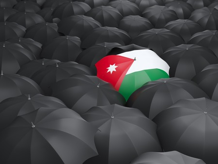 Umbrella with flag of jordan over black umbrellas photo