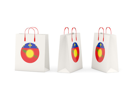 Round flag of guadeloupe on shopping bags. 3D illustration