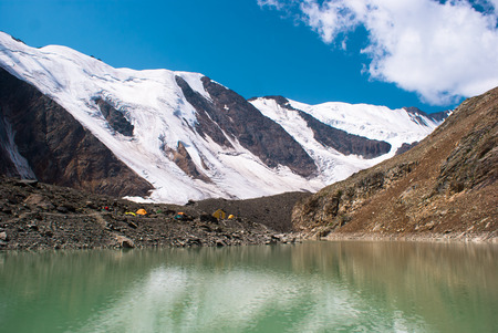 altay: Emerald lake with white snow peaks. Altay mountains.
