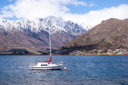 snow covered mountains: White boat in a lake with snow covered mountains, New Zealand