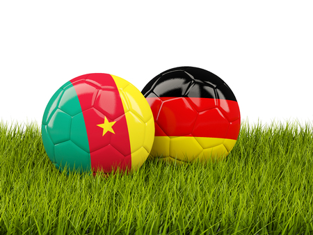 cameroon: Two footballs with flags of Cameroon and Germany on green grass. 3D illustration