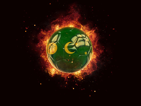 Football in flames with flag of cocos islands on black background. 3D illustration