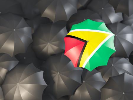 Umbrella with flag of guyana on top of black umbrellas. 3D illustration