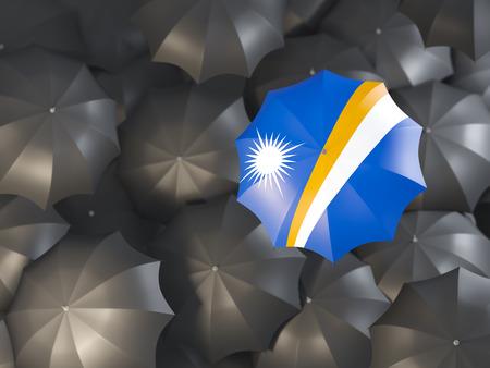 Umbrella with flag of marshall islands on top of black umbrellas. 3D illustration