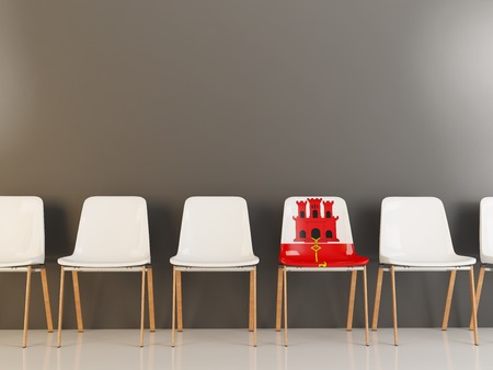 Chair with flag of gibraltar in a row of white chairs. 3D illustration