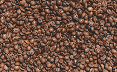 Closeup texture of coffee beans on the table. Coffee background