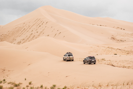 Two cars driven through sand dunes in Gobi desert. South east of Mongolia