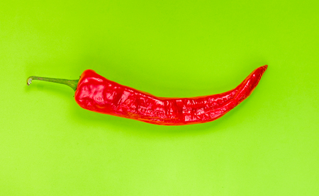 Red spicy chili peppers isolated on green background Stock Photo