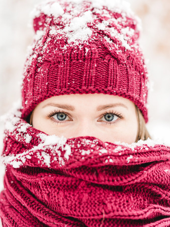 Close up portrait of a young woman with red hat and scarf outdoors in a winter forest