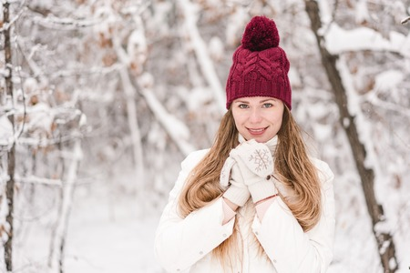 Smiling young woman outdoors in a winter forest covered with a fresh snow