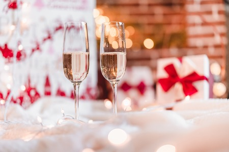 Two champagne glasses in front of christmas presents and sparkling background
