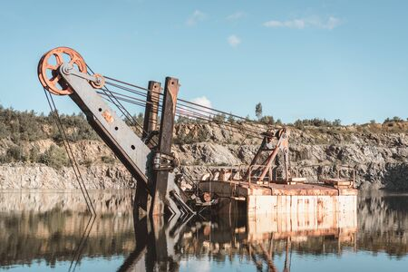 Rusting excavator in the middle of the lake. Old stone quarry
