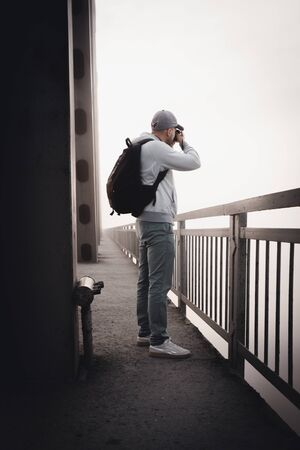 Photographer taking picture of the bridge in a heavy fog. Early morning