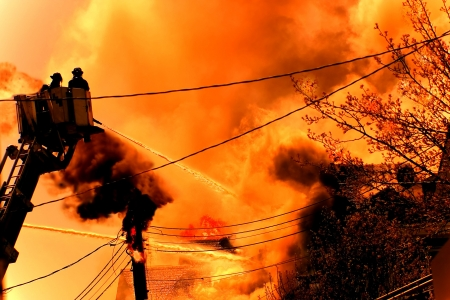 a huge fire with firefighters in action  Stock Photo