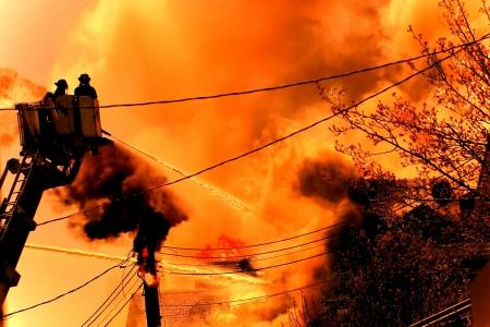 een enorme brand met brandweerlieden in actie