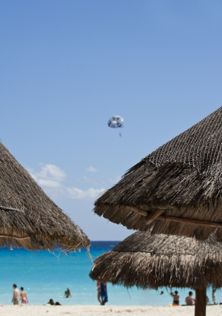 Straw umbrellas tops on resort beach photo