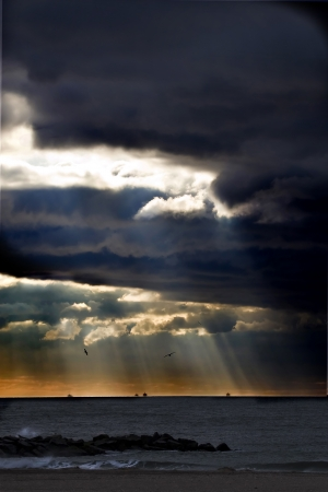 emanating: Sunbeams emanating through clouds above the ocean