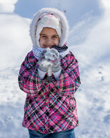 Beautiful little girl holding snow photo