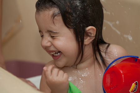 Happy laughing baby taking a bath. photo
