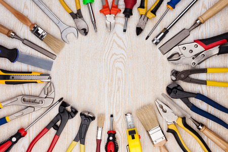 Work tools lined up in a circle on a wooden background  Stock Photo