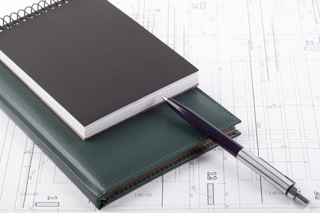 Notebooks and a pen on top of architectural drawings. photo